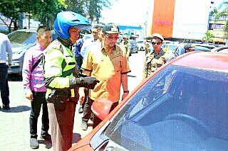 Menegur pemilik kendaraan yang parkir sembarangan.