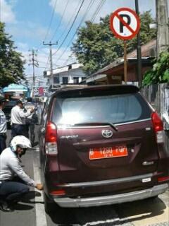 Kendaraan dinas milik pemerintah yang parkir ditempat terlarang.