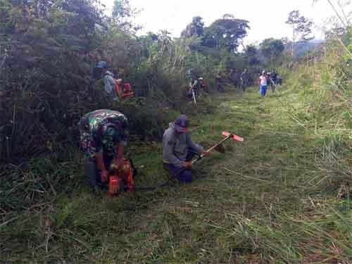 Anggot Satgas bersama warga mengerjakan pembukaan akses jalan antar desa. (foto: Penrem 132/Tadulako).