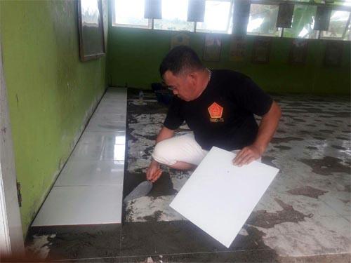 Proses pemasangan keramik lantai di ruang kelas SDN 23 Pangea.